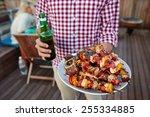 man serves skewer kebabs for... | Shutterstock . vector #255334885