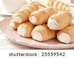 Elegant french cream horn pastries on decorative plate with cup and saucer in background.  Close-up with shallow dof. - stock photo