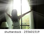 girl opening curtains in a... | Shutterstock . vector #255601519
