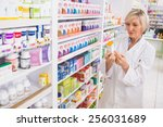 smiling pharmacist looking at... | Shutterstock . vector #256031689