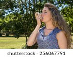 pretty blonde using her inhaler ...   Shutterstock . vector #256067791