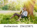 A nice looking man is sitting against a tree in the grass, looking like he is dreaming awake.  He is relaxing, enjoying the shadow of the tree in a sunny day.