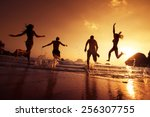 Stock photo group of happy young people is running on background of sunset beach and sea 256307755