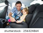 father securing baby in the car ... | Shutterstock . vector #256324864