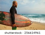 surfer at the sea is standing... | Shutterstock . vector #256614961