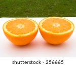 This is a close-up shot of two half oranges with some green grass in the background. - stock photo