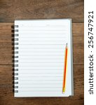 notebook and pencil on old wood. | Shutterstock . vector #256747921