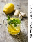 Small photo of tea with lemon and ginger, mint on a wooden background