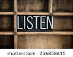 """Small photo of The word """"LISTEN"""" written in vintage metal letterpress type in a wooden drawer with dividers."""