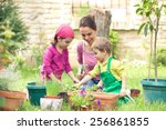 Young Mother Gardening In Fron...