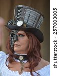 Small photo of Adult steampunk woman with eyewear and hat posing at the elf fantasy fair Elfia in Arcen, Netherlands on the 20th of September 2014.
