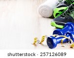 Small photo of Fitness concept with dumbbells and sneakers