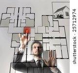a businessman touching a digital blueprint of home - stock photo