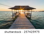 Stock photo tourist sitting on wooden jetty while watching a stunning sunrise on the sea togean or togian 257425975