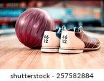 Small photo of Bowling equipment. Close up of bowling shoes and lilac ball lying on bowling alley