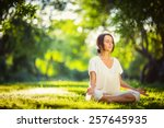 Stock photo young girl doing yoga in the park 257645935