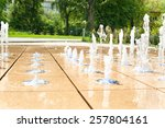Many small splashing dancing fountains in summer Warsaw park. Outdoors. - stock photo