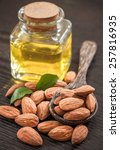 Small photo of Bottle almond oil and almond on wood background