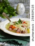 Small photo of Shchi - traditional russian cabbage soup on a wooden table.