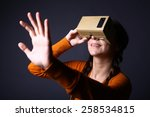 Stock photo color shot of a young woman looking through a cardboard a device with which one can experience 258534815