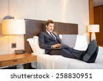 Stock photo working in hotel room confident young businessman in suit and tie working on laptop while sitting 258830951