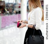 Small photo of Young stylish woman in cute trendy outfit with leather handbag looking into purse. Close-up on hands with wallet