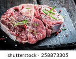 Meat with fresh herbs on black rock - stock photo