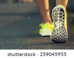 Stock photo runner woman feet running on road closeup on shoe female fitness model sunrise jog workout sports 259045955