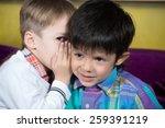 boy is telling a secret to a... | Shutterstock . vector #259391219