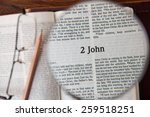 "Small photo of CHIANGMAI, THAILAND, March 3,2015. Reading The New International Version of the Holy Bible on the page of "" 2 john "" at home. March 3,2015"