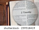 "Small photo of CHIANGMAI, THAILAND, March 3,2015. Reading The New International Version of the Holy Bible on the page of "" 2 timothy "" at home. March 3,2015"
