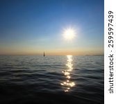 A Lone Sailboat In The Sun