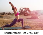 Stock photo young woman doing yoga in desert at sunrise time 259753139