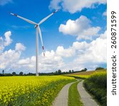 Small photo of agrarian landscape with blooming canola field and wind turbine