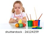 Little serious girl painting the easter eggs - stock photo