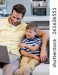 father and son using laptop on... | Shutterstock . vector #261636551
