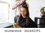 Small photo of beauty, hairstyle and people concept - happy young woman with smartphone and hairdresser making hair styling at salon