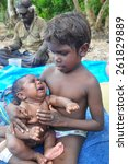 Small photo of AUSTRALIA - MAY 5: unidentified aborigine boy caring baby on May 5, 2014.Northern Territory, Australia
