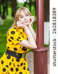 Small photo of Young woman in yellow dress has leant elbows on park lamppost.