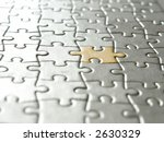 Background of silver puzzle pieces and one golden piece - selective focus - stock photo