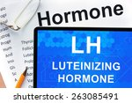 Small photo of Papers with hormones list and tablet with words luteinizing hormone (LH).