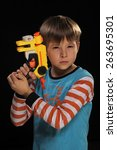 Small photo of A boy with a toy gun depicts a special agent.
