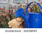 Blue metal watering can with stone wall, flowers and gloves in background.  Selective focus on spout with water droplets.  Shallow dof. - stock photo