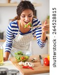 young woman eating fresh salad... | Shutterstock . vector #264528815