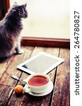 Stock photo blank tablet device over a wooden workspace table with cup of tea and cat selective focus 264780827