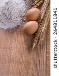 Small photo of organized copyspace heaf of four eggs corolla wheat ears on wooden board food and drink concept