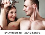 Small photo of Bodybuilding. Strong fit man exercising with dumbbells. Closeup muscular guy flexing lifting weights, lovely girl looking admiringly kissing his biceps.