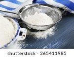 sifting flour through sieve on... | Shutterstock . vector #265411985