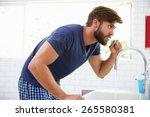 Man In Pajamas Brushing Teeth...