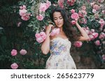 Stock photo beautiful young woman with long curly hair posing near roses in a garden 265623779